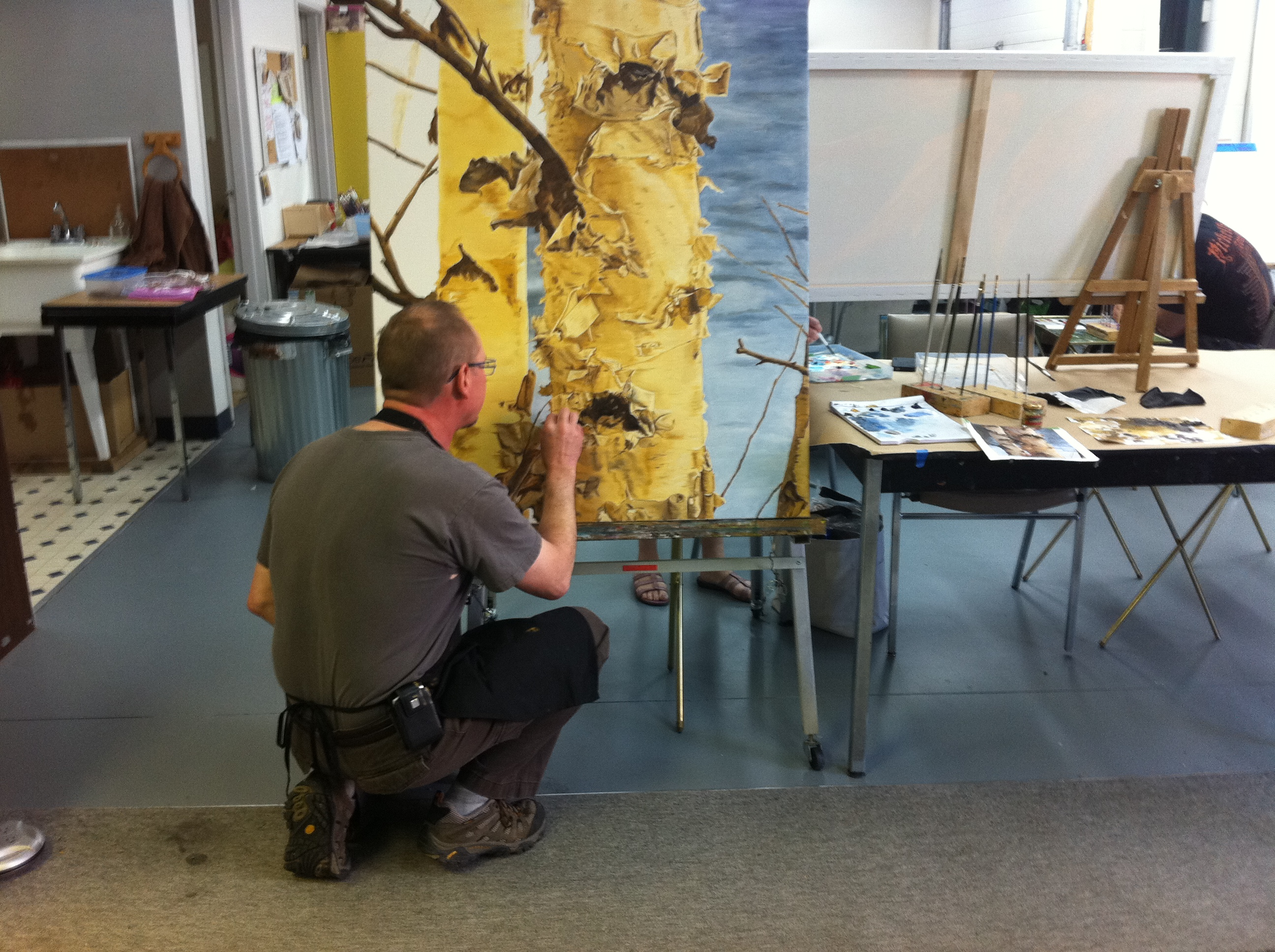 Color being added to a large birch tree oil painting.